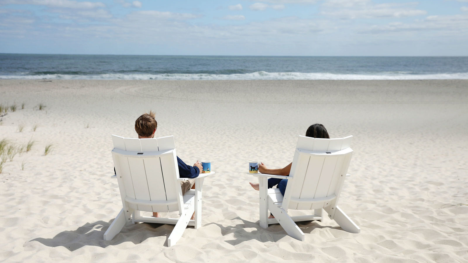 photo of two people sitting in beach chairs on a beach with beach dog mugs
