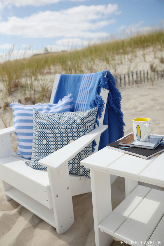 photo of a beach chair with pillows and blanket and a table with two books and a surfboard mug