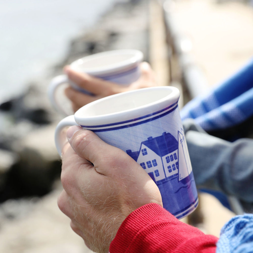 photo of two people's hands holding coastal village mugs