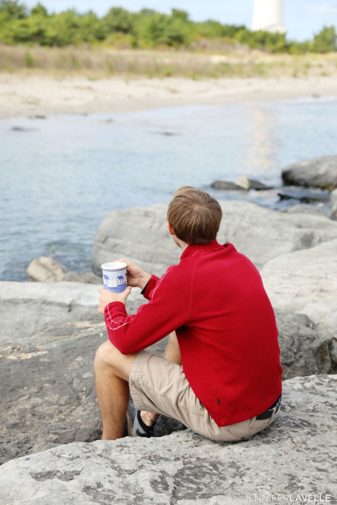 photo of a man sitting on a stone breakwater holding a coastal village mug