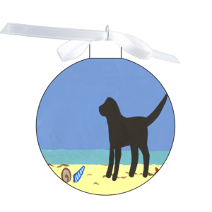 photo of the 80mm Ornament with a black dog on the beach