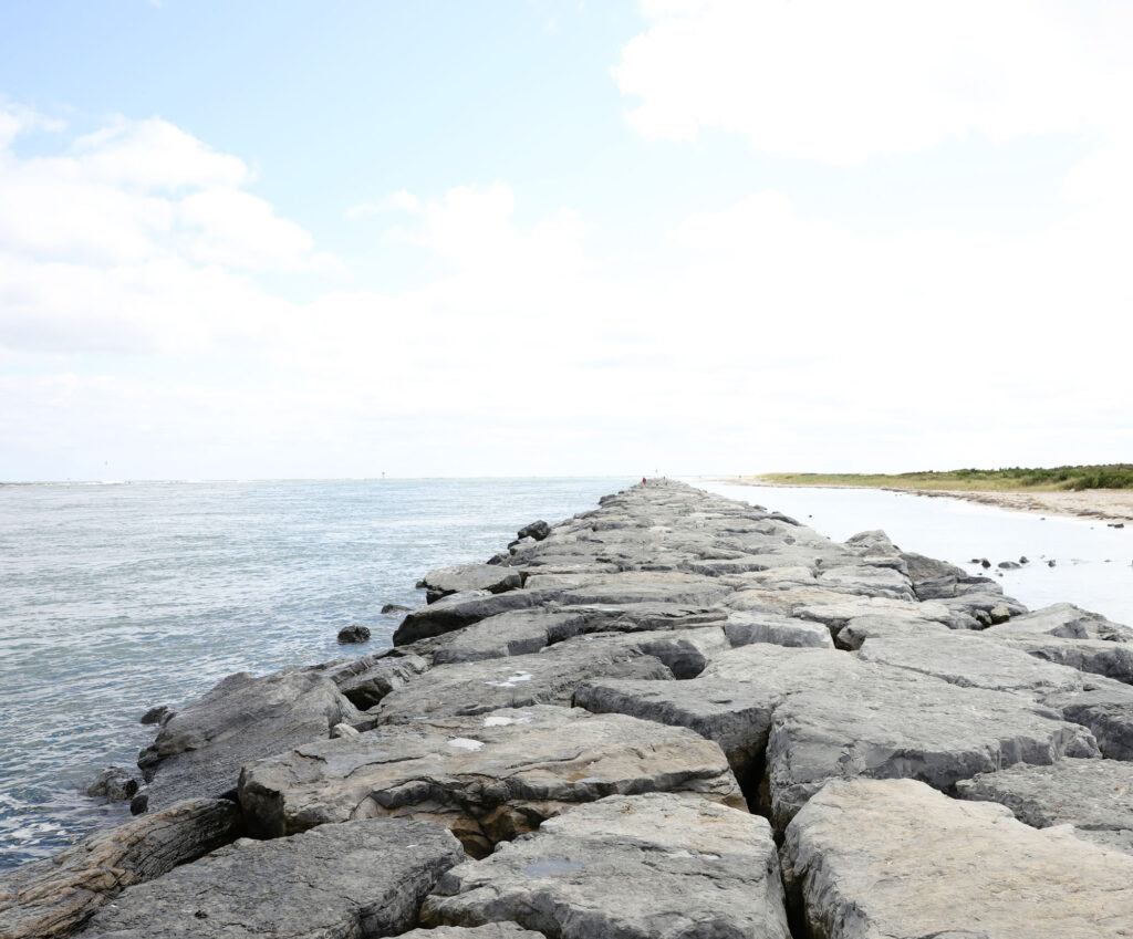 photo of a stone breakwater along a coast