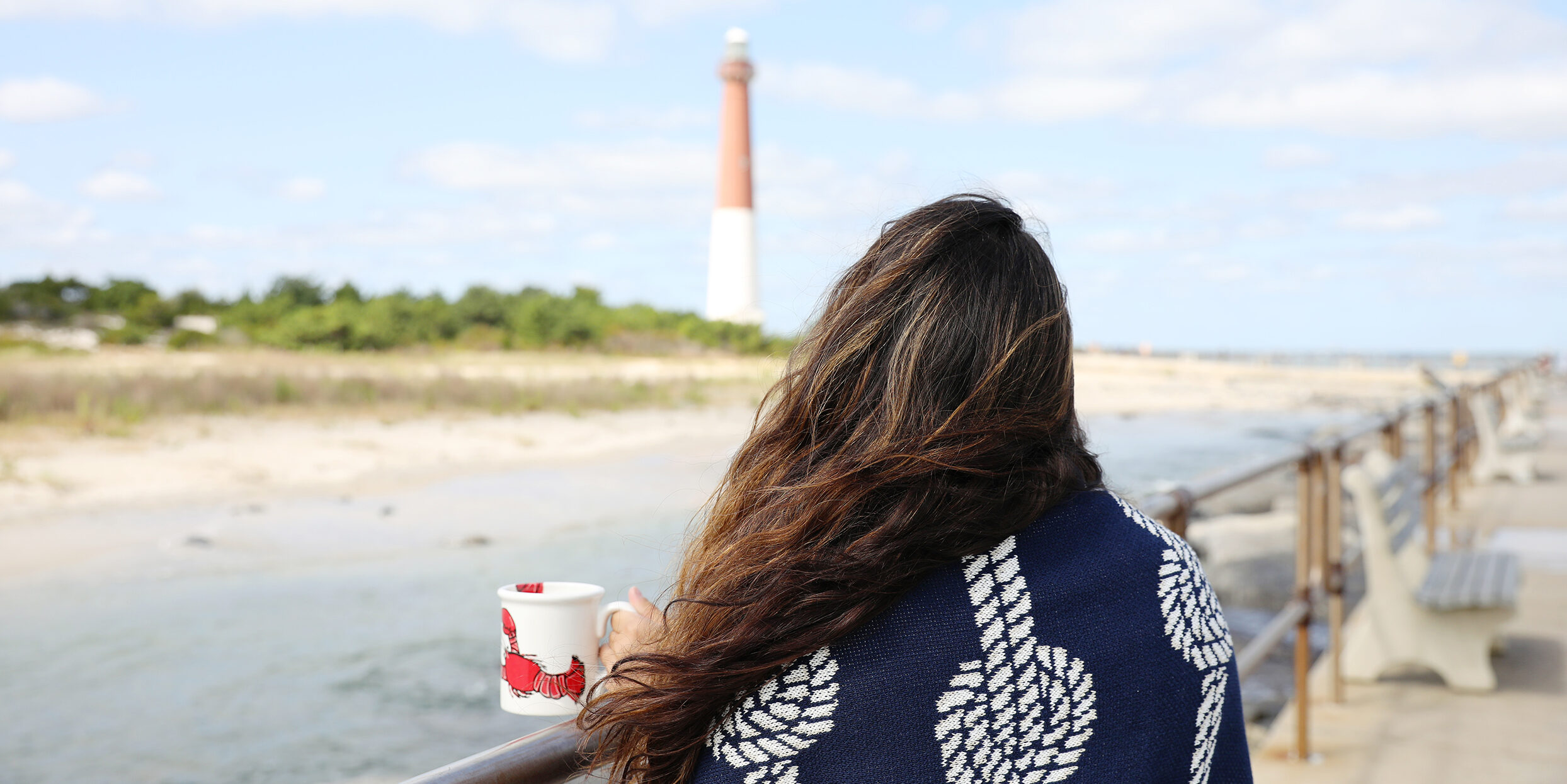 photo of a woman back turned to the camera looking at a lighthouse holding a coffee mug with a lobster on it